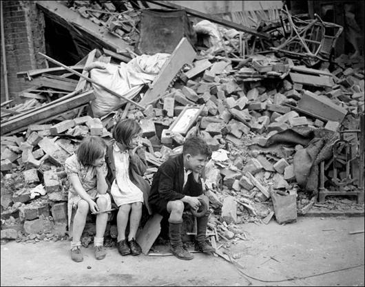 Three children sit in front of their remains of their home in the East End (September, 1940)