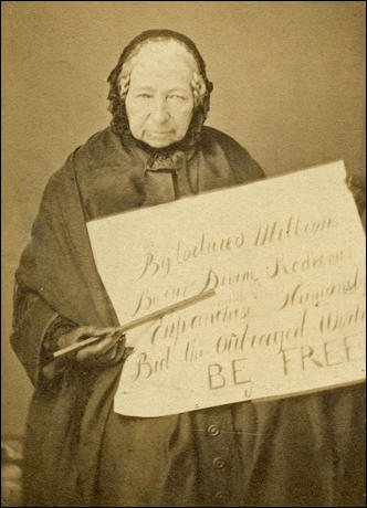 "Anne Knight, photograph by Victor Franck in about 1855. The placard reads: ""By tortured millions, By the Divine Redeemer, Enfranchise Humanity, Bid the Outraged World, BE FREE""."