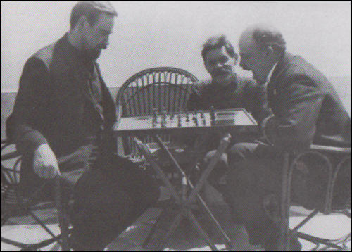 Lenin playing chess with Alexsandr Bogdanov in 1908. Maxim Gorky is seated between them.