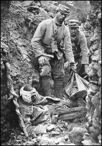 French soldiers try to move a wounded man alonga communication trench on the Western Front.