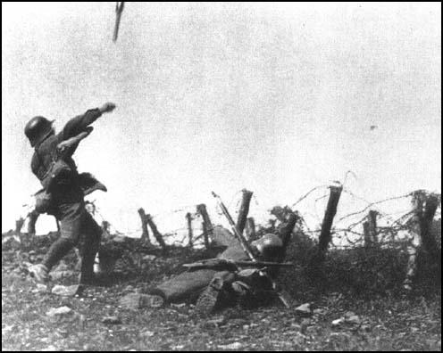 A German soldier throws a stick grenade during an attack on Allied trenches in 1918. He carries no other weapon and is protected by a rifleman who carries extra grenades.