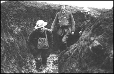 Officers walking through a flooded communication trench.