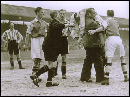 Ted Drake being carried off unconcious by Tom Whittaker in the match against Brentford on 18th April, 1938