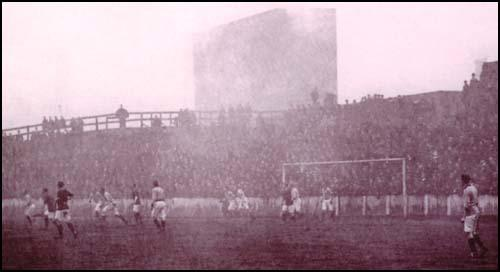 Manchester United playing a home game against Portsmouth in January 1907.The smoke was created by the chimneys of the adjacent chemical works.