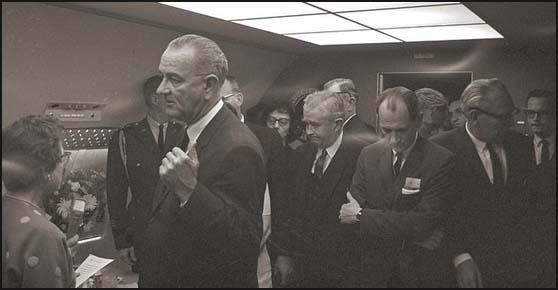 Photograph of a group waiting for the arrival of Jackie Kennedy for the swearing in ceremony. Left to right: Judge Sarah T. Hughes, Lyndon B. Johnson, Evelyn Lincoln, (background), Homer Thornberry, Jack Brooks (arms folded), Cliff Carter and Bill Moyers.