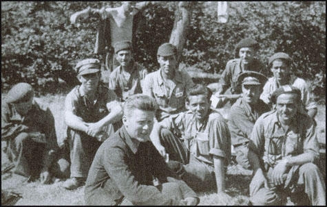 Sam Wild wearing a beret is kneeling on the right of the picture.