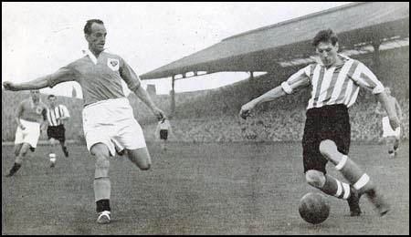 Harry Johnston of Blackpool tries to block a shot by Len Shackleton