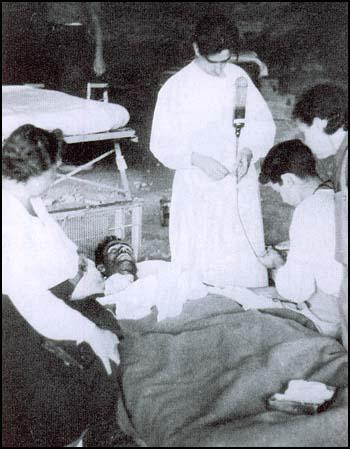 Harry Dobson receiving a blood transfusion fromReginald Saxton while receiving support from Leah Manning.