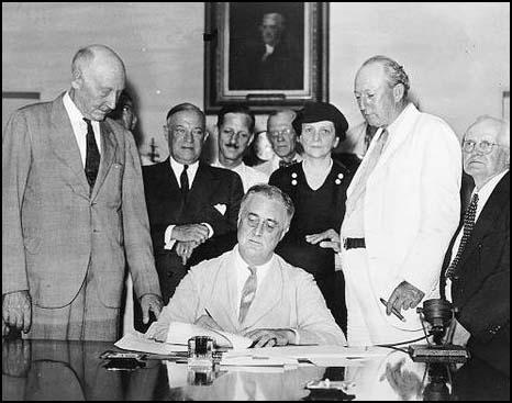 President Franklin D. Roosevelt signing the Social Security Act on 15th August, 1935. David John Lewis is on the right of the photograph.