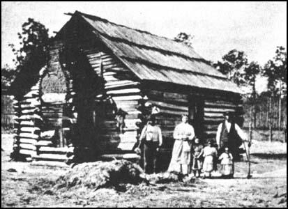 A slave family outside their cabin.