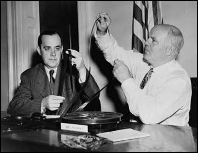 Robert E. Stripling and J. Parnell Thomas examine films to be shown to the House Un-American Activities Committee.