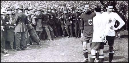 David Jack, with his hand on his hip, waiting for the police to clear the crowd from the pitch before the 1923 FA Cup Final.