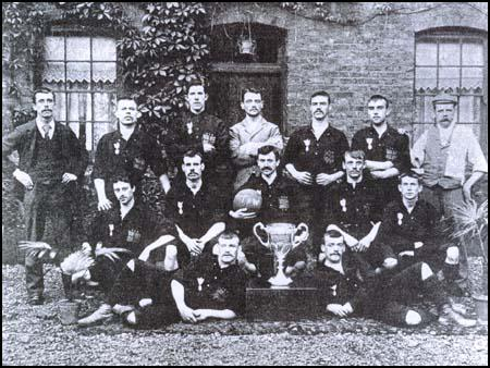 The Thames Iron Works team in 1896 with the West Ham Charity Cup. Back row (left to right): Arnold Hills, French, Graham, Francis Payne, John Woods, William Hickman and Tom Robinson (trainer). Centre; William Chamberlain, George Sage, William Faram, William Chapman, William Barnes. Front; Johnny Stewart, Thomas Freeman.